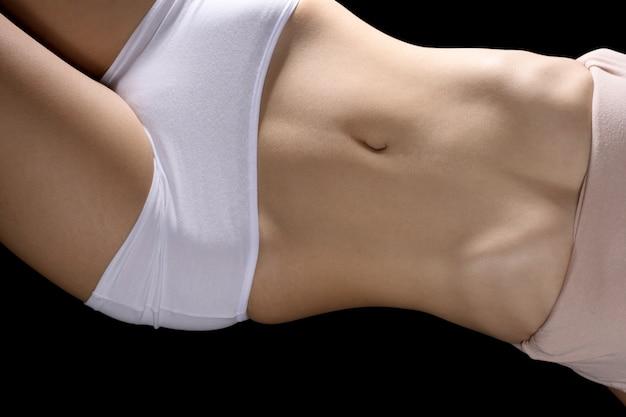 Partie de corps de femme asiatique peau bronzée s'allonger sur fond noir isolé