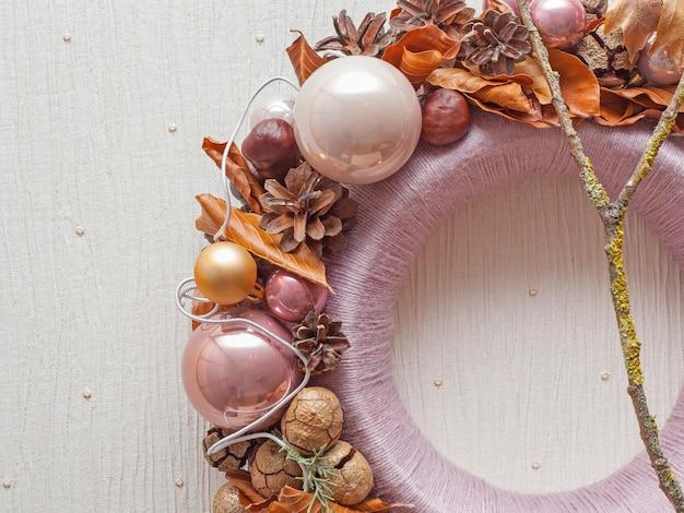 Partie de la couronne de décoration de noël avec des cônes et des jouets de noël sur fond beige. vue de face