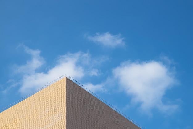 Une partie du bâtiment jaune clair sous le ciel bleu et les nuages blancs