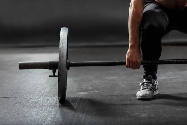 Une partie du bras et de la jambe de l'homme, soulevant une barre de gymnastique