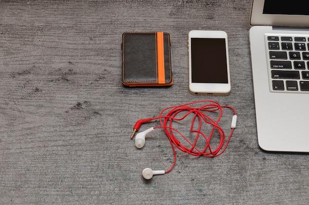 Une partie du clavier d'ordinateur portable, du portefeuille, du téléphone intelligent et des écouteurs.