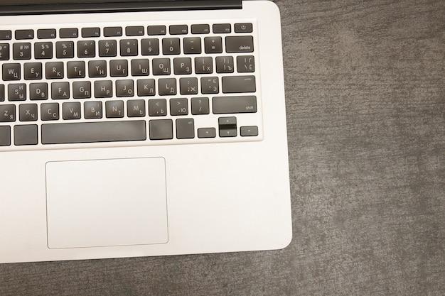 Une partie du clavier d'ordinateur portable sur une table en bois noire.