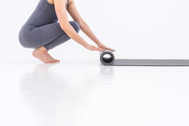 Une partie du corps d'une femme en gros plan dépliant un tapis de yoga sur fond blanc. mode de vie du yoga