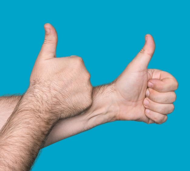 Partie du corps. signe de pouce en l'air. isolé sur fond bleu. concentrez-vous sur les poings