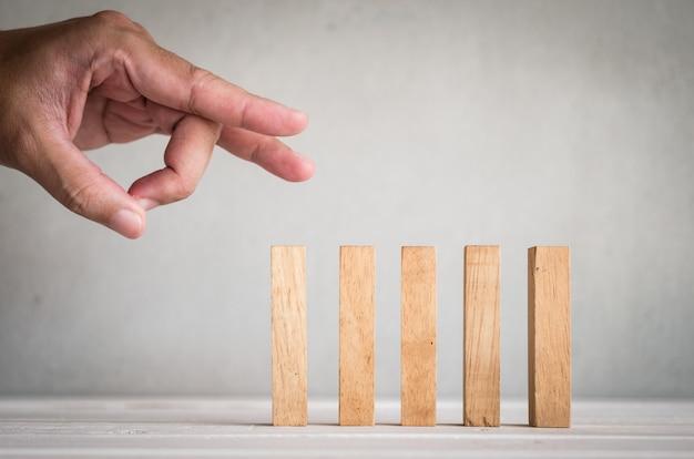 Partie du doigt humain pousser le domino en bois sur la table