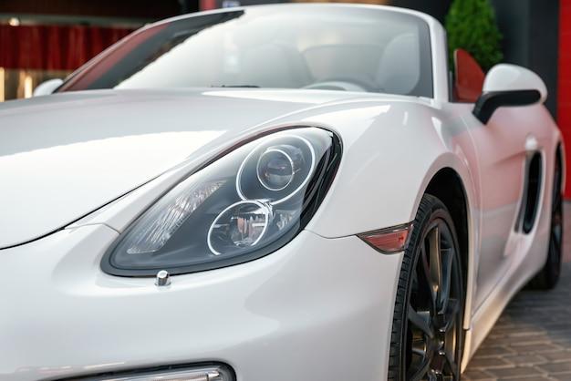 Une partie du nouveau parking moderne blanc à la porte du garage l'automobile une vue latérale sur une roue de luxe