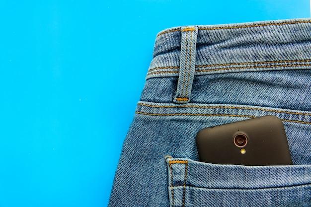Partie du téléphone portable dans la poche arrière d'un jean bleu