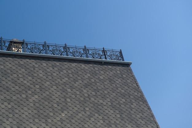 Une partie du toit avec des tuiles et une clôture métallique