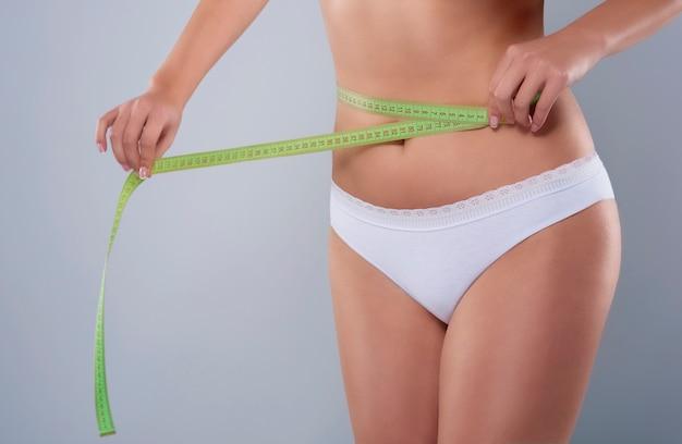 Partie de femme mesurant la taille