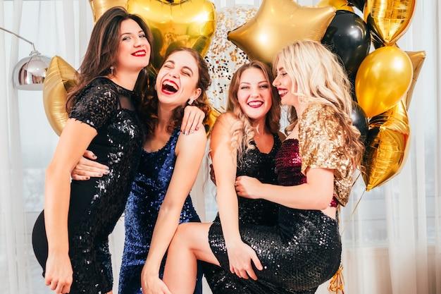 Partie de filles. ambiance festive positive. dames drôles en robes de cocktail, avec du maquillage du soir, posant, s'amusant, riant.
