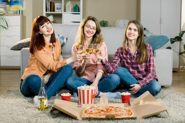 Partie de filles. occasion festive. dames en jeans et chemises décontractés. filles heureux tinter les verres avec du vin, rire, s'amuser. soirée pizza à la maison de trois amies