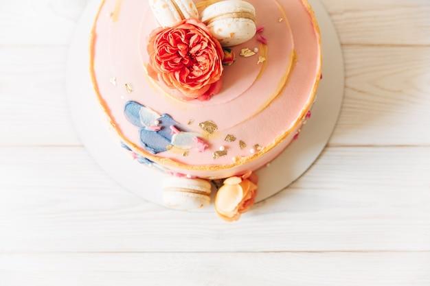 Partie de gâteau. rose clair avec des fleurs et des macarons. vue de dessus