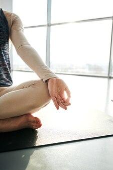Partie gauche de la jeune femme fit en vêtements de sport assis sur un tapis en pose de lotus et en gardant son index et son pouce ensemble pendant la formation