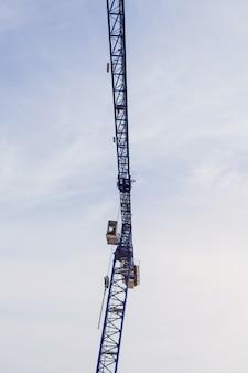 Une partie d'une grue à tour de construction contre le ciel bleu
