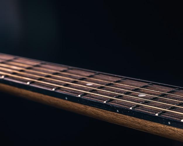 Partie d'une guitare acoustique, manche de guitare sur fond noir.