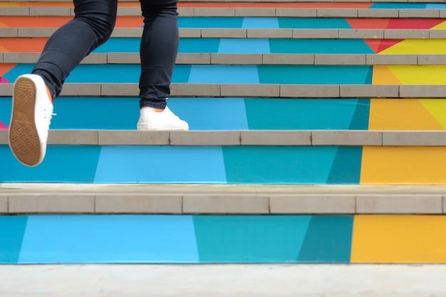 Partie inférieure d'une adolescente dans une chaussure décontractée qui monte l'escalier coloré extérieur