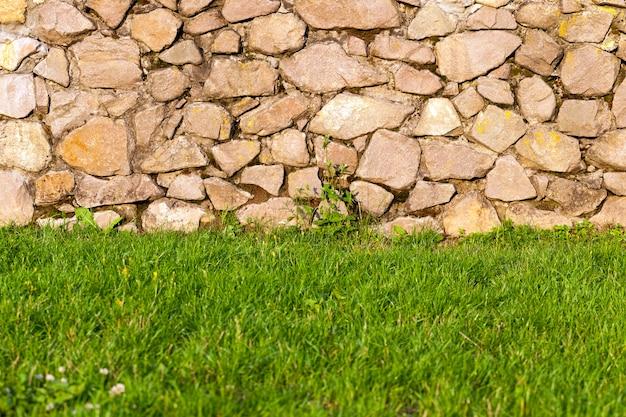 La partie inférieure du mur et la fondation de l'ancien bâtiment en pierres et en dessous pousse une herbe verte