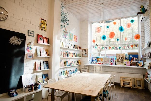 Partie de l'intérieur de la salle de classe avec table en bois au centre, tableau noir sur mur de briques et livres sur des étagères