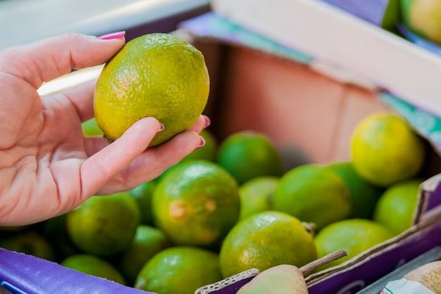 Partie intermédiaire de la femme qui achète du citron vert au supermarché. femme achetant des fruits dans un marché vert organique. femme choisissant de la citron vert