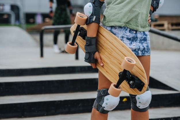 Partie médiane d'une patineuse en forme tenant une planche. au skatepark avec pavé en béton. position forte assumée.