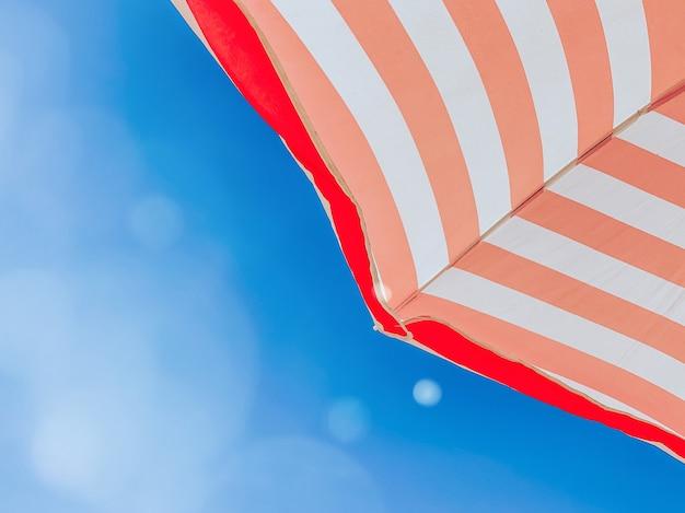 Partie d'un parasol à rayures contre un beau ciel bleu, vue de dessous. concept de tourisme et d'été, place pour le texte.