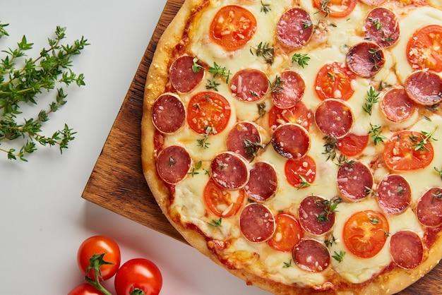 Partie de pizza au pepperoni italien maison chaude avec salami, mozzarella sur tableau blanc