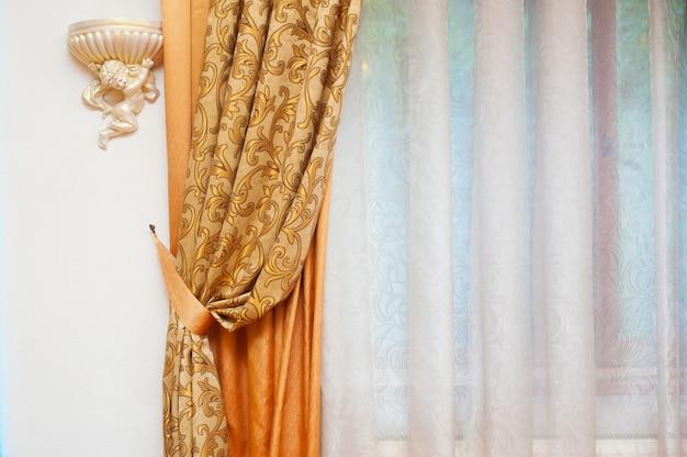 Partie d'un rideau magnifiquement drapé et d'un mur avec des motifs