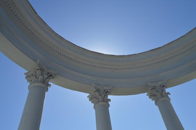 Partie d'une rotonde blanche avec des colonnes sur un ciel bleu par une journée ensoleillée.