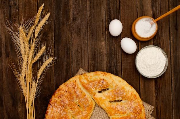 Une partie de la tarte sur un sac, des œufs, de la farine et du sel