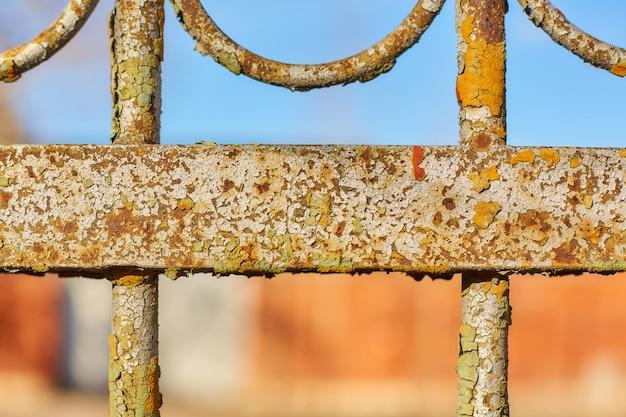 Partie d'une vieille clôture de fer rouillée avec un ciel bleu