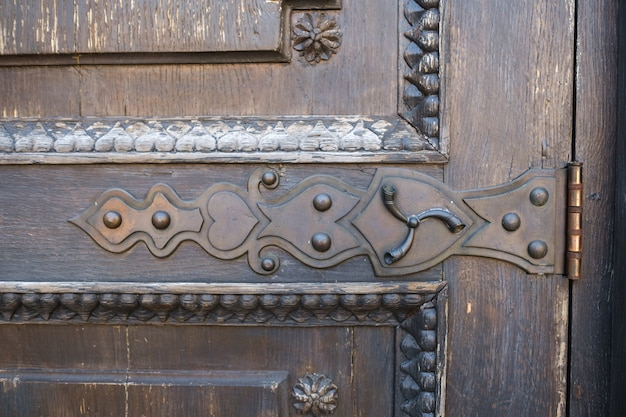 Partie d'une vieille porte en bois avec un motif de vitrail.