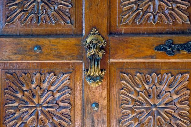 Partie de la vieille porte en bois avec poignée en or sculpté