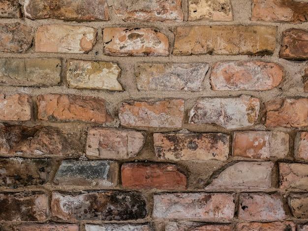 Partie d'un vieux mur de brique patiné en rouge et brun