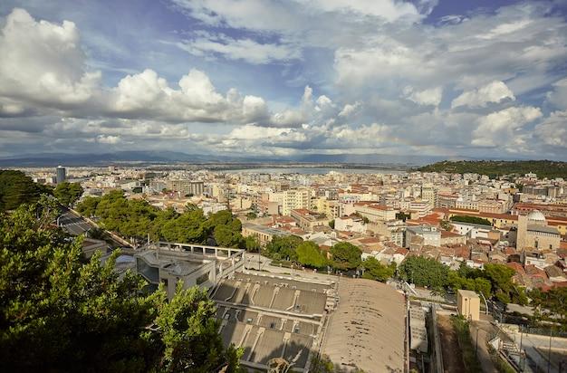 Partie de la ville de cagliari prise d'en haut avec un ciel plein de nuages blancs