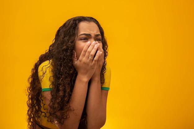 Partisan brésilien de belle jeune femme aux cheveux bouclés.