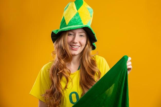 Partisan du brésil. fan de femme rousse brésilienne célébrant le football, match de football aux couleurs du brésil. porter un t-shirt, un drapeau et un chapeau de fan.