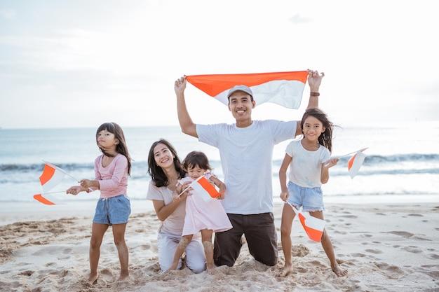 Partisan de la famille indonésienne enthousiaste avec le drapeau indonésien sur la plage ensemble