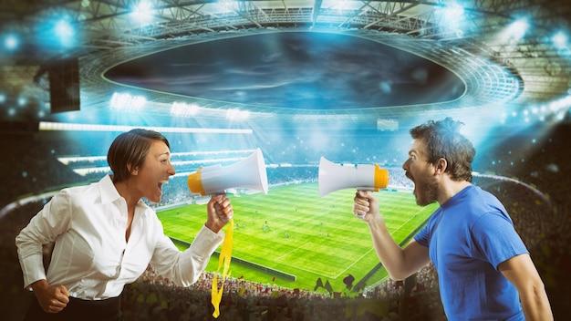 Les partisans des équipes adverses se crient les uns contre les autres avec un mégaphone dans le stade lors d'un match de football
