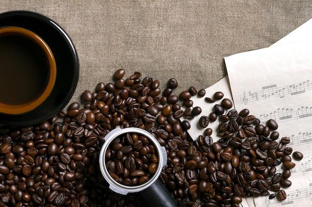 Partitions de grains de café et tasse de café sur un fond de toile de jute