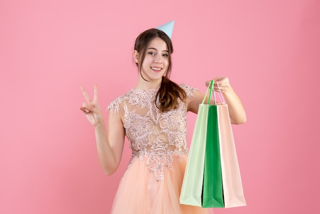 Party girl with party cap holding shopping bags faisant signe de victoire sur rose