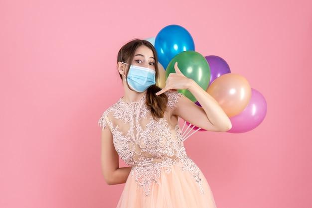 Party girl with party cap tenant des ballons colorés derrière son dos faisant appelez-moi signe sur rose