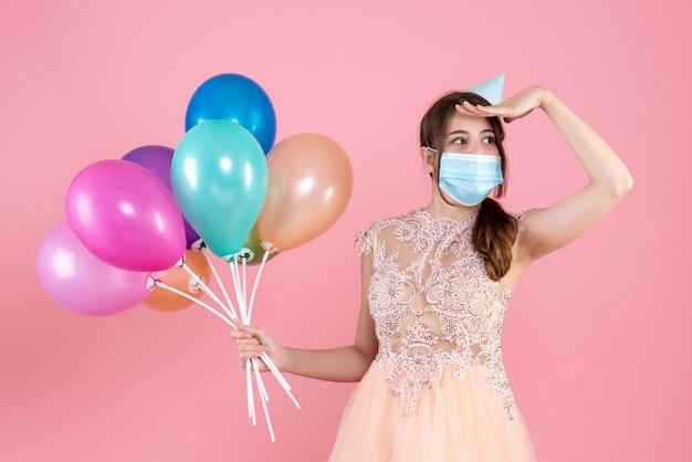 Party girl with party cap tenant des ballons colorés mettant la main sur son front sur rose