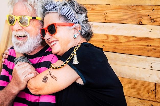 Pas d'âge limite avec un couple caucasien de personnes âgées sympa et drôle, s'amuser et sourire dans un portrait avec une scène en bois
