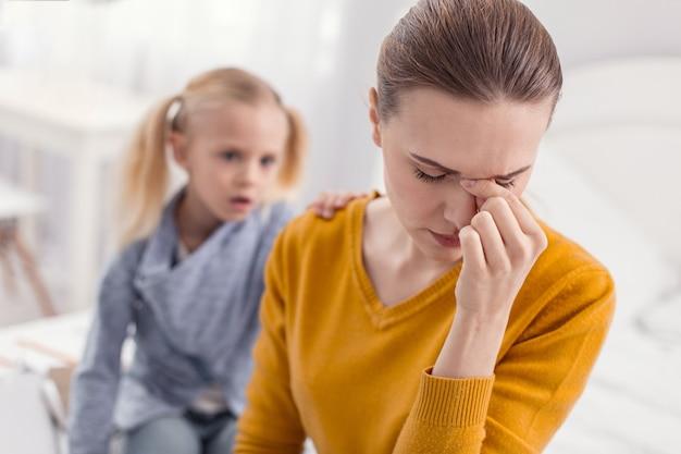 Pas assez de temps. jeune mère séduisante déprimée touchant le pont du nez tout en fermant les yeux et posant sur le flou