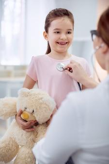 Pas de difficultés. fille joyeuse inspirée tenant un ours en peluche et debout pendant que la femme médecin l'examinait