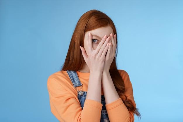 Pas furtivement promesse charmante intriguée mignonne adolescente rousse cachant le visage couvrir les yeux paumes regarder à travers les doigts vérifier cadeau anticipant quelque chose d'intéressant debout curieux fond bleu