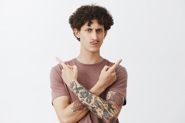 Pas sûr d'hésiter un jeune homme mignon avec des cheveux noirs bouclés et une moustache fantaisie souriant et fronçant les sourcils méfiant et douteux pointant à gauche et à droite de différents côtés ne peut pas choisir quel choix