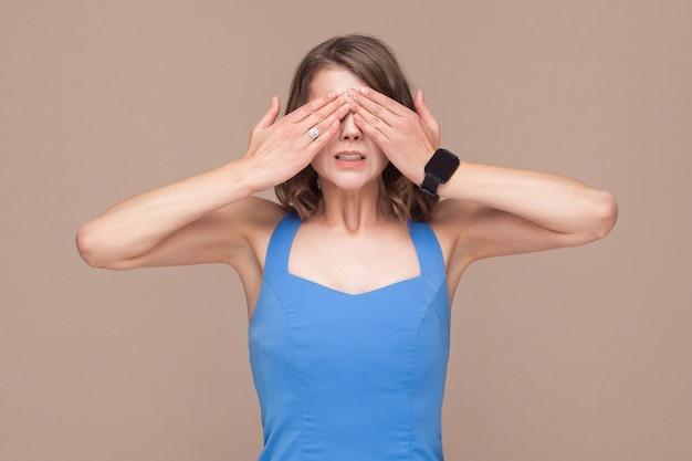 Pas intéressant. femme en robe bleue a fermé les yeux ses mains. prise de vue en intérieur
