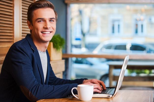 Pas de minute sans mon ordinateur portable. beau jeune homme travaillant sur ordinateur portable et souriant tout en dégustant un café au café