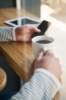 Pas de minute sans technologies. gros plan d'un homme tenant une tablette numérique tout en dégustant un café au café